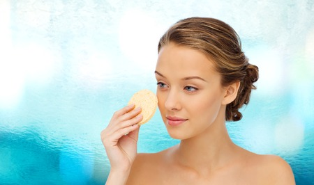 removing make up: beauty, people and skincare concept - young woman cleaning face with exfoliating sponge over blue water background