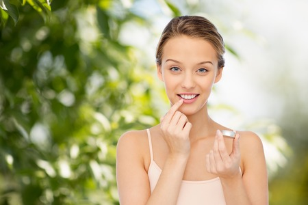 beauty, people and lip care concept - smiling young woman applying lip balm to her lips over green natural background Imagens
