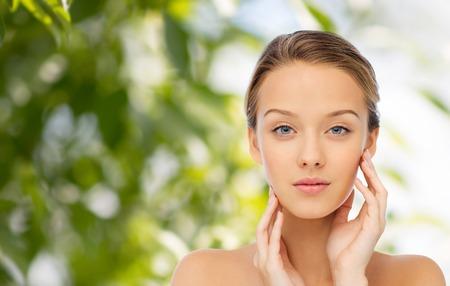 La belleza, la gente y el concepto de salud - mujer joven con los hombros descubiertos que toca su cara sobre el fondo verde natural Foto de archivo - 52076314
