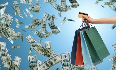 cash card: people, sale, finance and consumerism concept - close up of male hand holding shopping bags and bank or credit card over blue background and money rain
