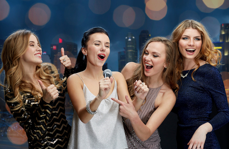holidays, friends, bachelorette party, nightlife and people concept - three women in evening dresses with microphone singing karaoke over city and lights background Stock Photo
