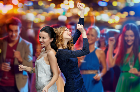 dancing club: party, holidays, nightlife and people concept - happy young women dancing at night club disco over night lights background