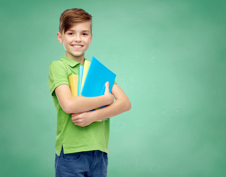 school boy: childhood, school, education and people concept - happy smiling student boy with folders and notebooks over green school chalk board background Stock Photo