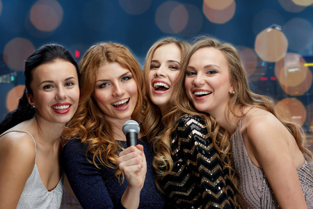 night out: holidays, friends, bachelorette party, nightlife and people concept - three women in evening dresses with microphone singing karaoke over lights background