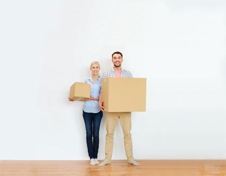 집, 사람, 수리 및 부동산 개념 - 행복한 커플 판지 상자를 들고와 새로운 장소로 이동