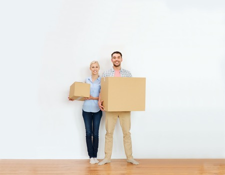 home, people, repair and real estate concept - happy couple holding cardboard boxes and moving to new place Фото со стока