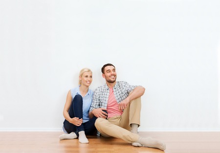 home planning: home, people, repair, moving and real estate concept - happy couple of man and woman sitting on floor and dreaming at new place Stock Photo