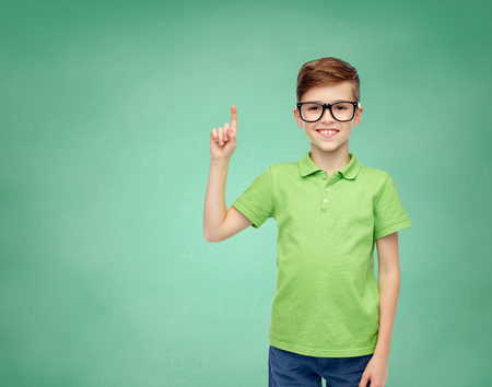 pre teen boys: childhood, vision, school, education and people concept - happy smiling boy in green polo t-shirt in eyeglasses pointing finger up over green school chalk board background Stock Photo
