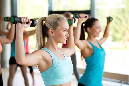 aerobics: fitness, deporte, entrenamiento y estilo de vida concepto - grupo de mujeres con pesas en el gimnasio Foto de archivo