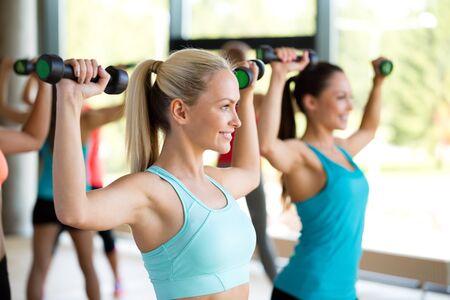 fitness, deporte, entrenamiento y estilo de vida concepto - grupo de mujeres con pesas en el gimnasio