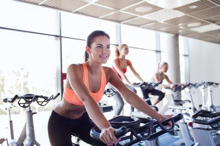 sport, fitness, styl życia, sprzęt i pojęcie osoby - grupa kobiet jeżdżących na rowerze stacjonarnym w siłowni