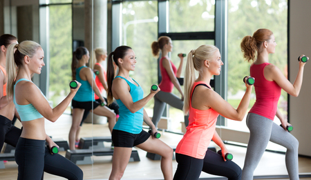 aerobics: fitness, sport, training, gym and lifestyle concept - group of women working out with dumbbells and steppers in gym