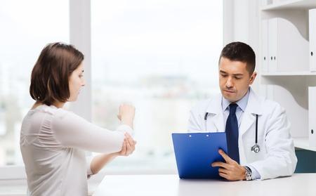 la medicina, la salud y las personas concepto - mujer joven que muestra el codo al doctor con el sujetapapeles y reunión en el hospital Foto de archivo