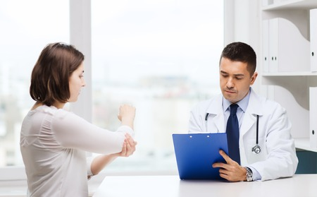 middle joint: medicine, health care and people concept - young woman showing elbow to doctor with clipboard and meeting at hospital Stock Photo