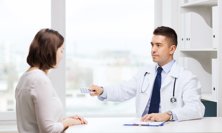 doctor giving pills: medicine, health care, medication and people concept - doctor with clipboard giving pills to young woman at hospital