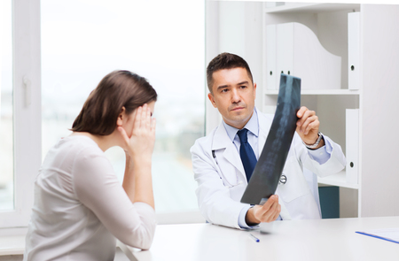 orthopedist: healthcare, surgery, rontgen, people and medicine concept - smiling male doctor in white coat with laptop computer looking at x-ray in medical office