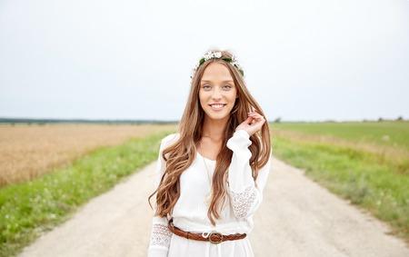 mujer hippie: naturaleza, verano, la cultura juvenil y la gente concepto - mujer hippie joven con corona de flores en el campo de cereales sonriendo Foto de archivo