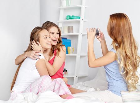 amistad, gente, fiesta pijama y el concepto de la tecnología - amigos felices o adolescentes con el teléfono inteligente que toma el cuadro en el hogar