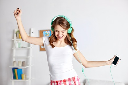 teenage girls: people, leisure and technology concept - happy woman or teenage girl in headphones listening to music from smartphone and dancing on bed at home