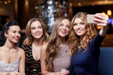 celebration, friends, bachelorette party, technology and holidays concept - happy women with smartphone taking selfie at night club Foto de archivo