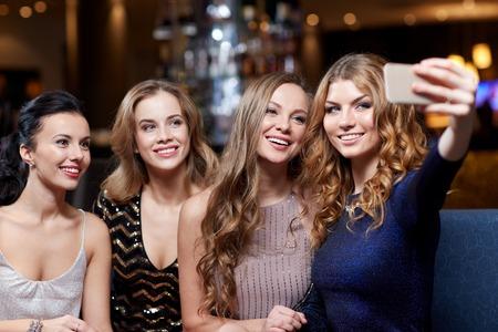 despedida de soltera: celebración, amigos, despedida de soltera, la tecnología y el concepto de vacaciones - mujer feliz con teléfono inteligente teniendo autofoto en el club nocturno