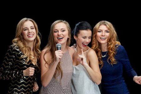 cantando: d�as de fiesta, amigos, fiesta del bachelorette, vida nocturna y el concepto de personas - tres mujeres en vestidos de noche con karaoke canto del micr�fono sobre el fondo negro Foto de archivo