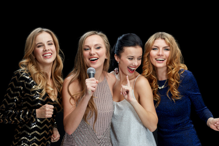 karaoke singer: holidays, friends, bachelorette party, nightlife and people concept - three women in evening dresses with microphone singing karaoke over black background