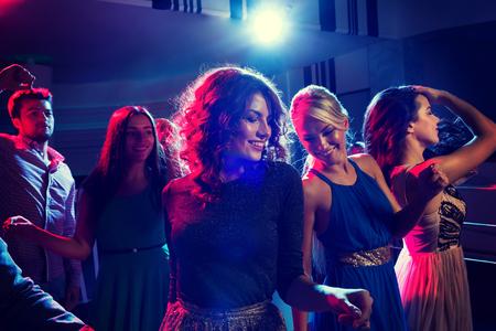 Party, Urlaub, Feiern, Nachtleben und Menschen Konzept - lächelnde Freunde tanzen im Club Lizenzfreie Bilder