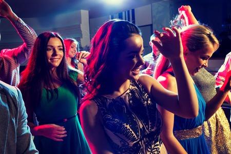 Party, Urlaub, Feiern, Nachtleben und Menschen Konzept - lächelnde Freunde tanzen im Club Standard-Bild