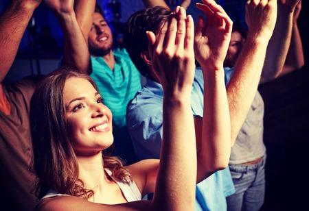 personas saludandose: fiesta, días de fiesta, celebración, vida nocturna y la gente concepto - sonriendo amigos que aplauden en concierto en el club