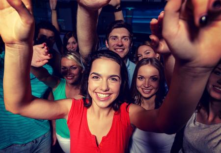 multitud gente: fiesta, días de fiesta, celebración, amigos y personas concepto - sonriente amigos bailando y agitando las manos en el club