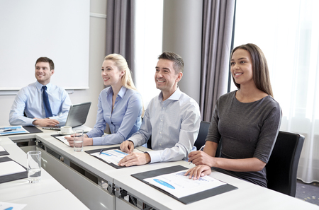 multiracial: business, people and conference concept - smiling business team meeting on presentation in office Stock Photo