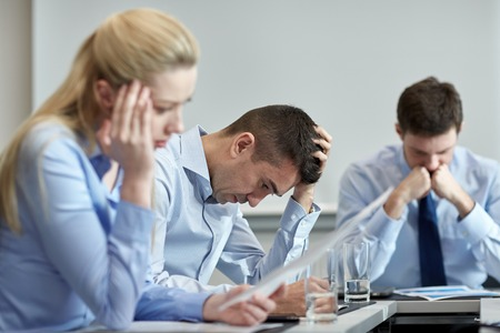 stressed business woman: business, teamwork, people and crisis concept - business team sitting sad and solving problem in office