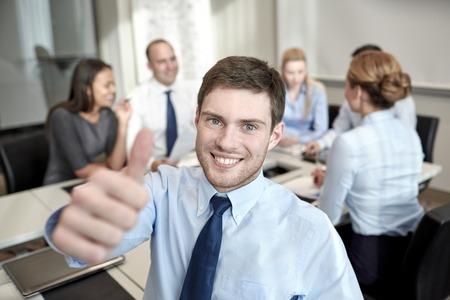비즈니스, 사람, 제스처와 팀워크 개념 - 사무실에서 기업인 회의의 그룹과 함께 사업가 엄지 손가락을 보여주는 미소