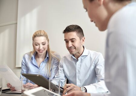 professional woman: business, people, technology and teamwork concept - smiling businessman and businesswomen with tablet pc computer meeting in office