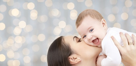 family, motherhood, children, parenthood and people concept - happy mother kissing her baby over holidays lights background Foto de archivo