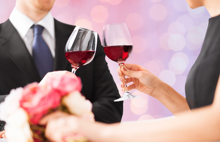 people, holidays, marriage and celebration concept - happy engaged with flowers clinking wine glasses over holidays lights background Stock Photo