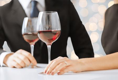 gente, días de fiesta, el casarse, oferta y el concepto de la joyería - manos de la pareja con el anillo y copas de vino de compromiso de diamantes en el restaurante más de fondo de las luces