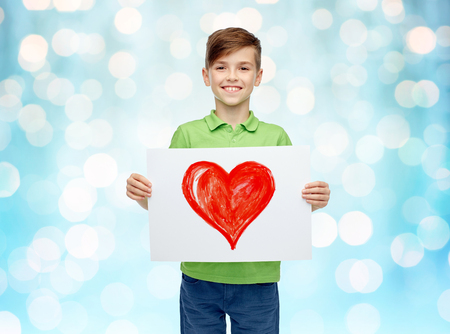 pre teen boy: childhood, creativity, art and people concept - happy smiling boy holding drawing or picture of red heart over blue holidays lights background Stock Photo
