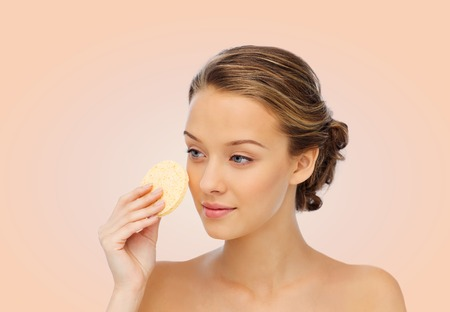 removing make up: beauty, people and skincare concept - young woman cleaning face with exfoliating sponge over beige background