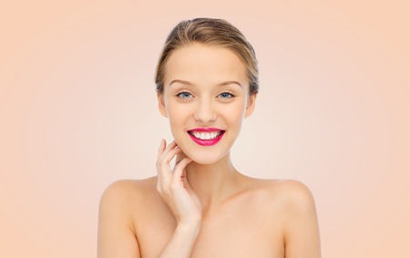 beige lips: beauty, people and health concept - smiling young woman face with pink lipstick on lips and shoulders over beige background