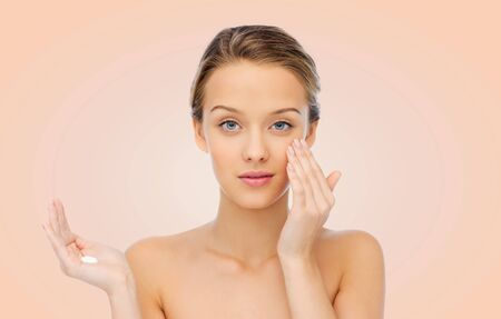 woman face cream: beauty, people, cosmetics, skincare and health concept - young woman applying cream to her face over beige background Stock Photo