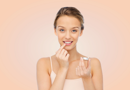 young woman: beauty, people and lip care concept - smiling young woman applying lip balm to her lips over beige background Stock Photo