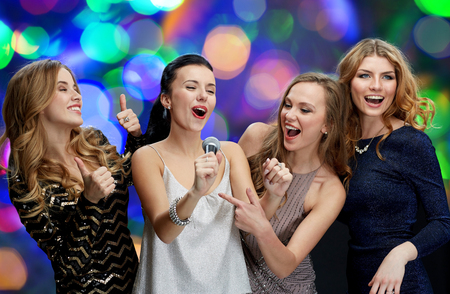 people laughing: holidays, friends, bachelorette party, nightlife and people concept - three women in evening dresses with microphone singing karaoke over lights background