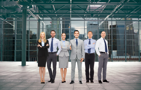 business partnership: business, people, partnership and cooperation concept - group of smiling businesspeople over empty urban city construction background Stock Photo