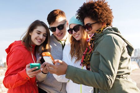friendship: people, friendship, cloud computing and technology concept - group of smiling teenage friends with smartphone outdoors
