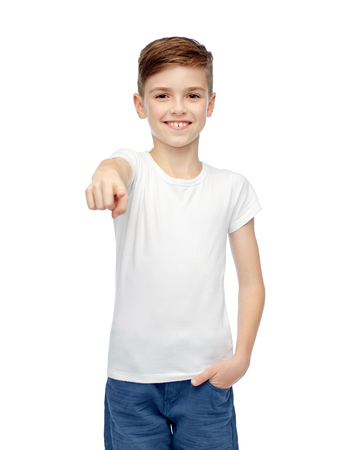 ten empty: childhood, fashion, advertisement and people concept - happy boy in white t-shirt and jeans pointing finger to you Stock Photo