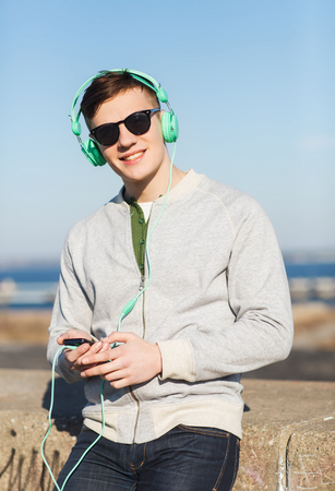 personas escuchando: tecnolog�a, estilo de vida y concepto de la gente - sonriente joven o adolescente en los auriculares con el tel�fono inteligente escuchar m�sica al aire libre