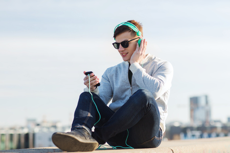 people listening: technology, lifestyle and people concept - smiling young man or teenage boy in headphones with smartphone listening to music outdoors Stock Photo