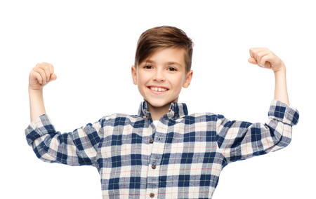 pre adolescent boys: childhood, power, strength and people concept - happy smiling boy in checkered shirt showing strong fists